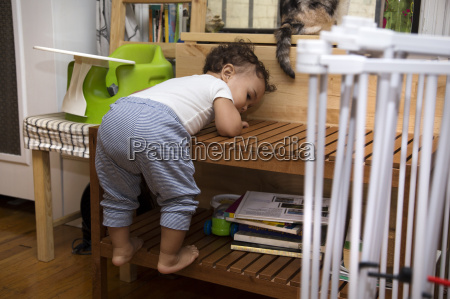 independent female toddler climbing coffee table