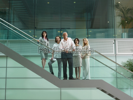 five office workers standing on stairs