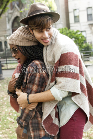 young male hipster hugging girlfriend in