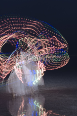 woman dancing and swirling illuminated multi