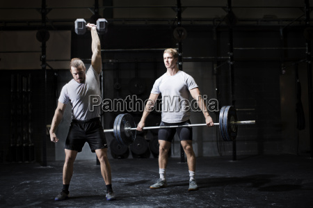 two young men weightlifting with dumbbell