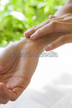 close up of woman moisturising hand
