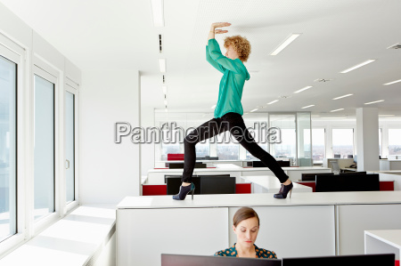 businesswoman standing on filing cabinet stretching