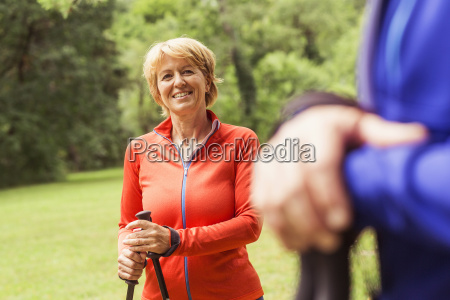 couple walking outdoors using walking poles