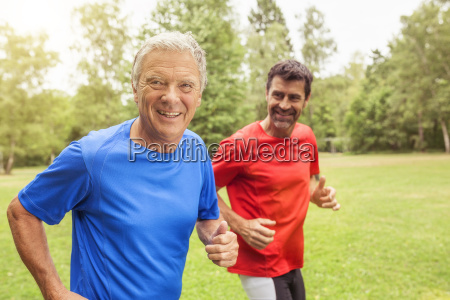 two men running outdoors smiling