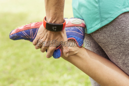 mature woman holding foot stretching mid