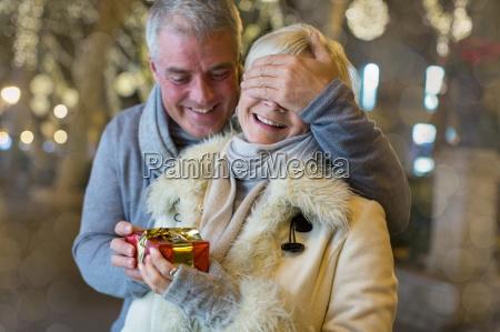 mature man handing with xmas gift