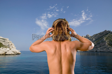 young man with headset at sea