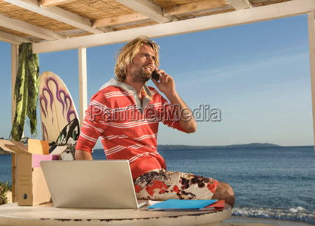 surf man on phone and laptop