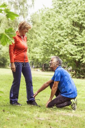couple exercising outdoors senior man holding