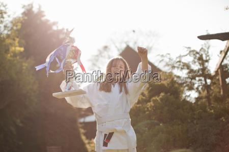 portrait of joyous girl celebrating trophy