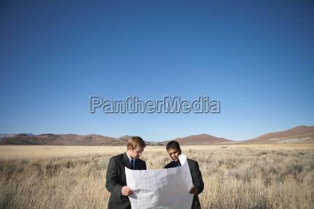 2 men examining blueprints in field
