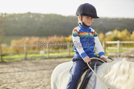 boy riding white pony in equestrian