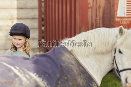 girl and pony looking over their