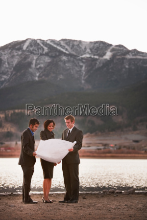 2 men and a woman examine