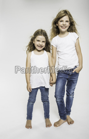 studio portrait of two sisters holding