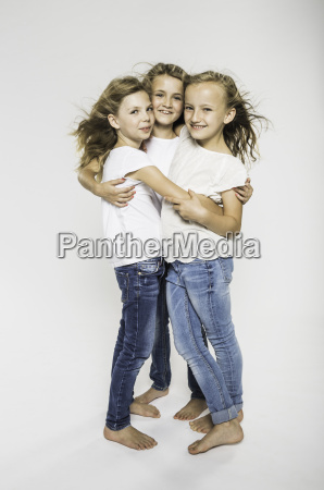 studio portrait of three girls hugging