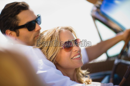 young couple driving convertible