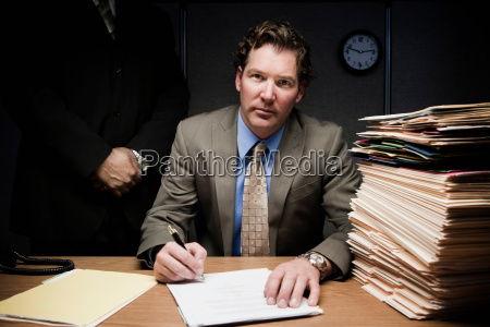 man doing paperwork with man behind