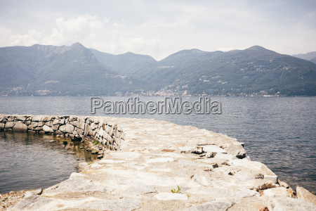 stone pier curving through water by