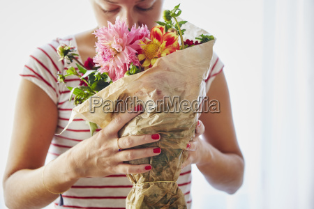 mid adult woman smelling bunch of
