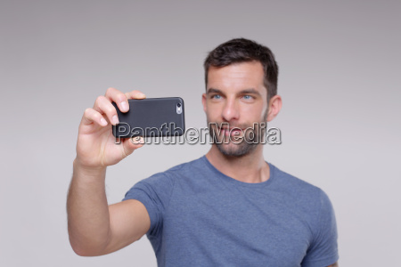 mid adult man taking photograph using