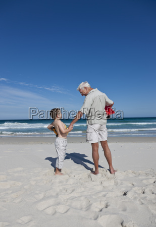 man holding grandsons hand on beach