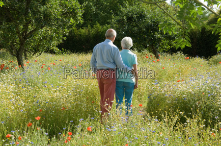 older couple walking in field of