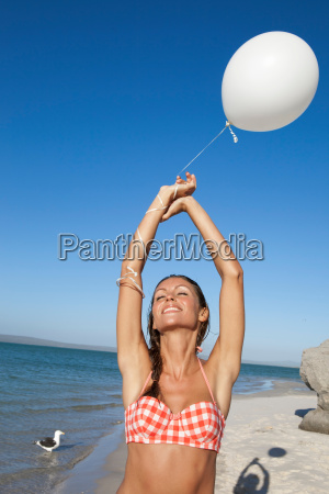 woman playing with balloon on beach