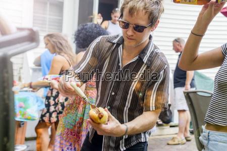 mid adult man preparing hotdog at