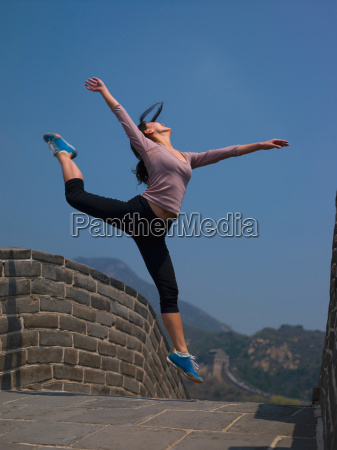 woman jumping on great wall of