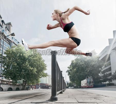 athlete jumping over banister on street