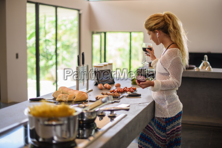 young woman multi tasking whilst preparing