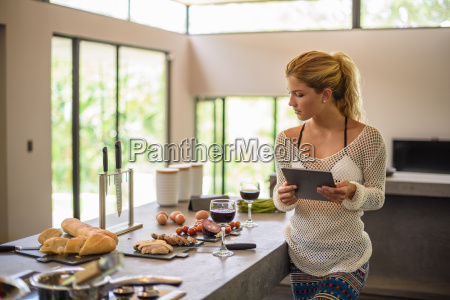 young woman using digital whilst preparing