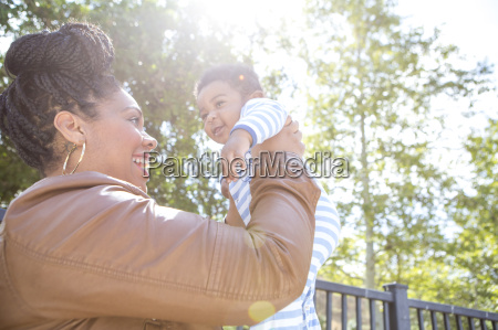 mother holding up baby boy in