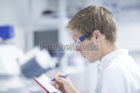 male scientist writing in notebook in