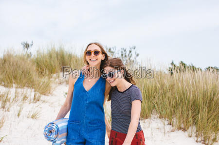 two young female friends on sand