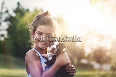 girl holding boston terrier puppy cheek