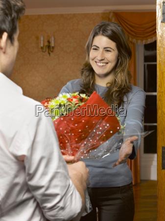man offering bouquet to girlfriend