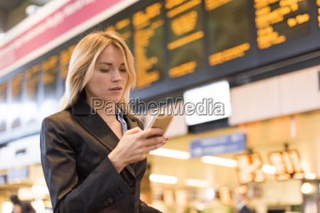 young businesswoman in railway station reading