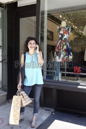 mature woman exiting fashion boutique carrying