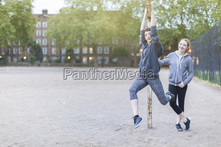young woman hanging from goal post