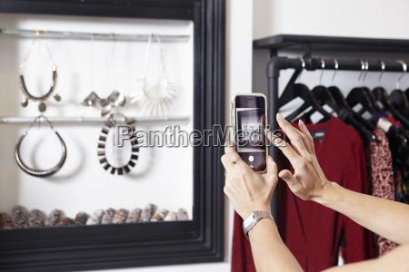 mature woman taking photograph of jewellery
