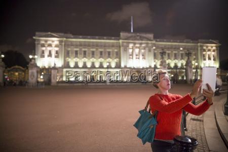 mature female tourist taking digital tablet