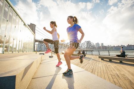 two female running friends running up