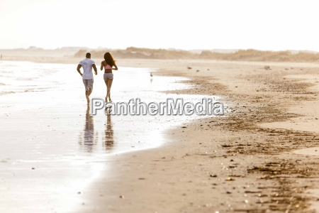 couple running along beach rear view