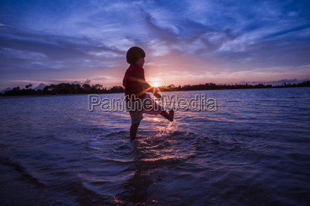 young boy paddling in sea sunset