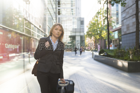young businesswoman with wheeled suitcase waiting
