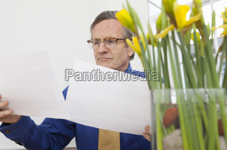 businessman reading papers at desk