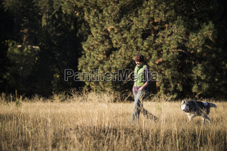mid adult woman walking dog in